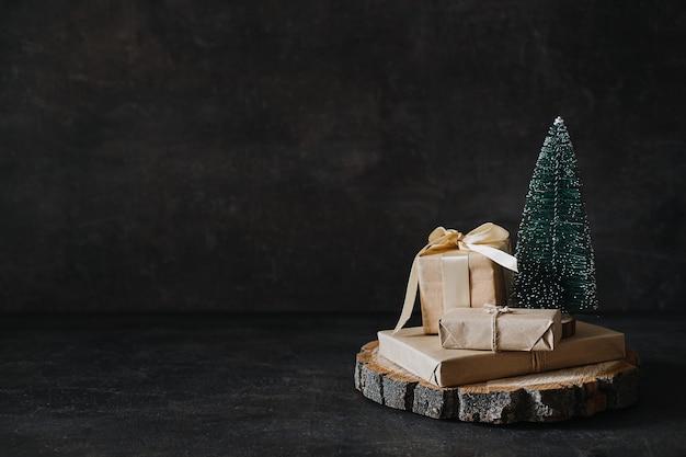 Weihnachtsbanner xmas minimaler dunkler hintergrund mit handwerksgeschenkboxen und kegelspielzeugweihnachtsbaum auf