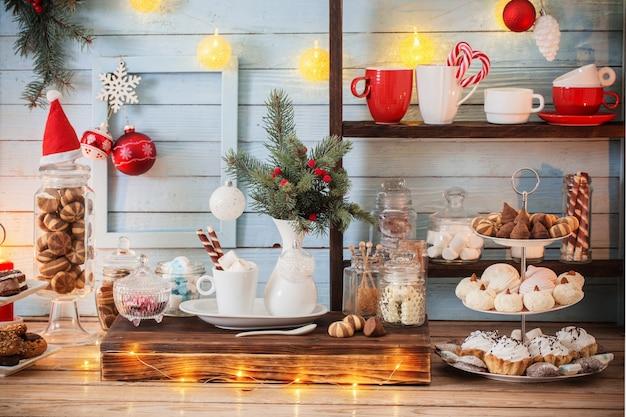 Weihnachtsbar-kakaodekoration mit keksen und süßigkeiten auf blauem hölzernem hintergrund im weinlesestil