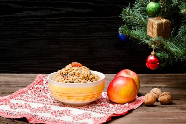 Weihnachtsbaum, äpfel, walnüsse auf einer gemusterten tischdecke