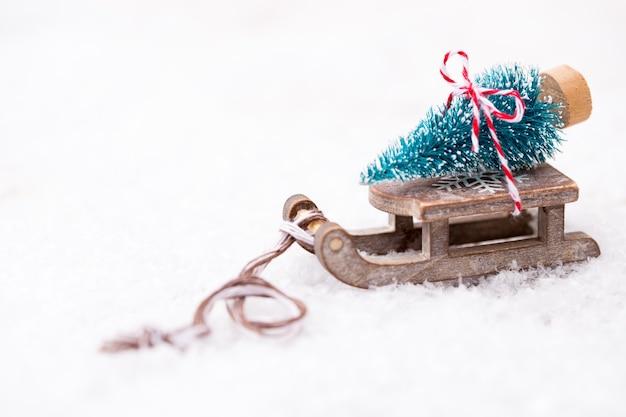 Weihnachtsbaum auf dem schlitten. goldthemaoberfläche für weihnachten und neujahr.