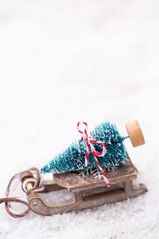 Weihnachtsbaum auf dem schlitten. weihnachten und neujahr goldthema hintergrund.