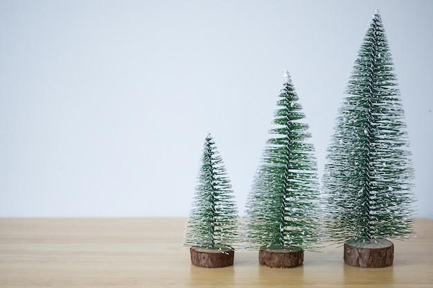 Weihnachtsbaum auf holztisch mit weißem wandhintergrund