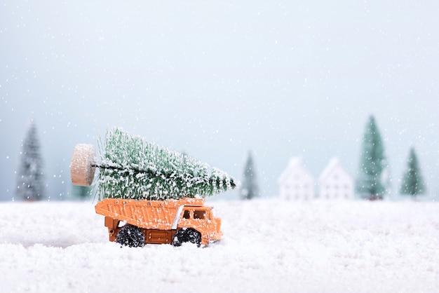 Weihnachtsbaum auf spielzeugauto-lkw lief durch den schnee im feld des natürlichen landschaftshintergrunds.