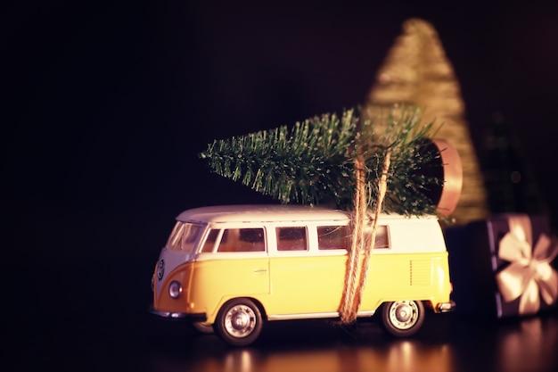 Weihnachtsbaum auf spielzeugauto. spielzeugauto mit weihnachtsbaum. weihnachtsfeiertagsfeierkonzept