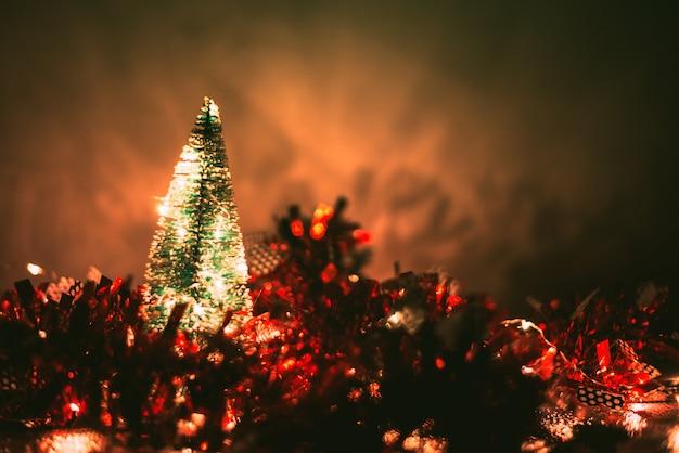 Weihnachtsbaum auf unscharfer weihnachtsdekoration und schneebedecktem hintergrund.