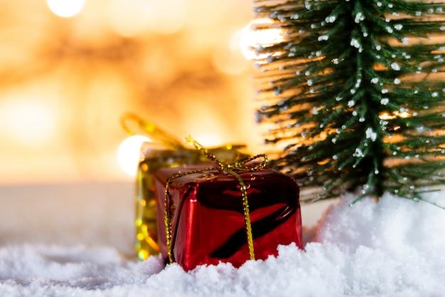 Weihnachtsbaum auf weißem schnee mit geschenk und hellen bokeh hintergründen