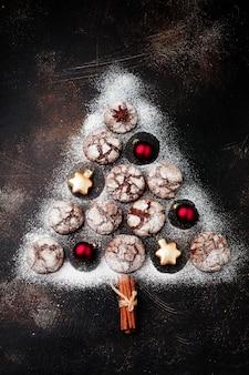 Weihnachtsbaum aus brownie-keksen mit rissen, zimtgewürzen, glocken und weihnachtsspielzeug auf alter beton- oder steinoberfläche. neujahrskonzept