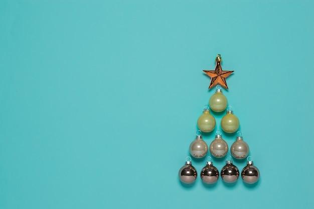 Weihnachtsbaum aus glaskugeln mit einem stern auf einer blauen oberfläche