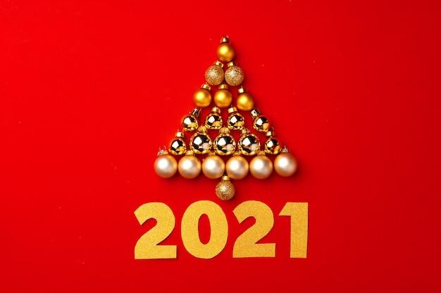 Weihnachtsbaum aus goldkugeln auf rotem hintergrund draufsicht
