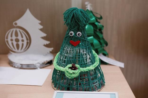Weihnachtsbaum aus grünen fäden, hergestellt in amigurumi-technik. handgefertigt, kieferndekoration. selektiver fokus.
