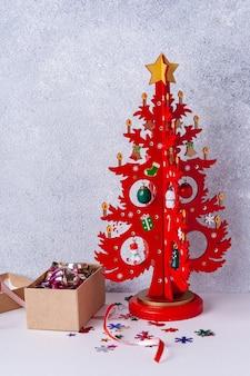Weihnachtsbaum aus holz rot und eine kiste mit spielzeug