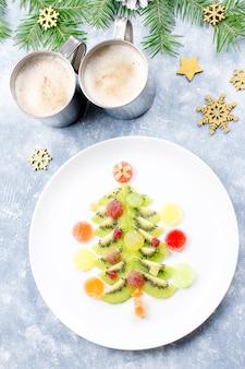 Weihnachtsbaum aus kiwi und fruchtgelee auf einem teller mit tannenzweigen und dekorationen. ansicht von oben, textfreiraum