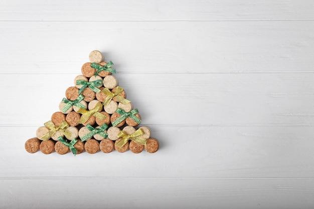 Weihnachtsbaum aus korkstopfen und bändern auf holzuntergrund