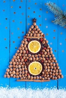 Weihnachtsbaum aus nüssen und getrockneten früchten auf dem hölzernen hintergrund mit sternen, schnee und tannenzweig