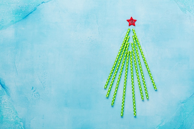 Weihnachtsbaum aus trinkendem buntem papier auf blauer oberfläche
