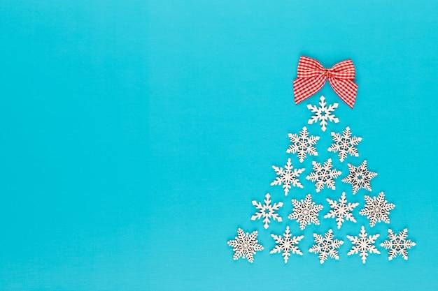 Weihnachtsbaum aus weißen schneeflockendekorationen auf rotem hintergrund mit leerem kopienraum für text. neujahrs- und weihnachtspostkarte.