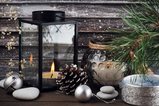 Weihnachtsbaum, brennende kerze und silberdekor im skandinavischen stil