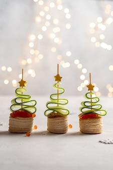 Weihnachtsbaum canape mit gurkenscheibe, lachspastete und rotem kaviar für festlichen weihnachtssnack