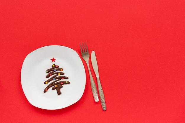 Weihnachtsbaum der süßen schokolade auf platte und tischbesteck