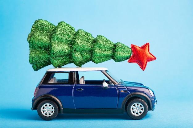 Weihnachtsbaum des neuen jahres mit rotem stern auf blauem autospielzeugdach. blauer farbhintergrund. kreativer miniatur-weihnachtsbaum auf dem auto.