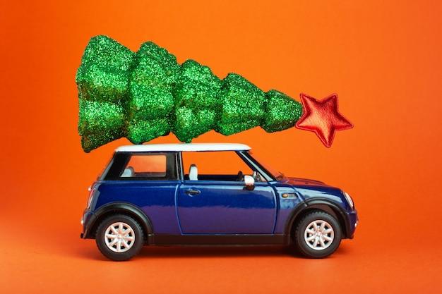 Weihnachtsbaum des neuen jahres mit rotem stern auf blauem autospielzeugdach. orangefarbener hintergrund. kreativer miniatur-weihnachtsbaum auf dem auto.