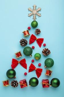 Weihnachtsbaum einer sammlung kleiner stücke zur dekoration auf blauem hintergrund. ansicht von oben