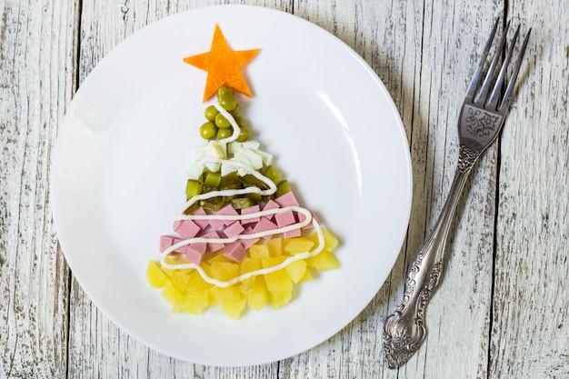 Weihnachtsbaum fromsalad olivier in der platte auf einem weißen holztisch. ansicht von oben
