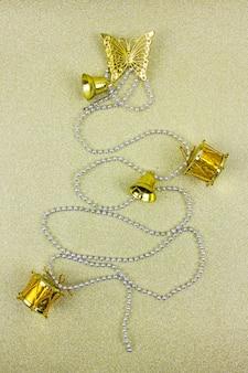 Weihnachtsbaum gemacht von den goldenen winterdekorationen auf goldhintergrund mit leerem kopienabstand