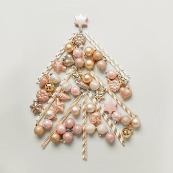 Weihnachtsbaum gemacht von den verschiedenen formen der silbernen glaskugeln, sterne, herz auf grauem hintergrund. weihnachtskonzept. flache lage, draufsicht, kopienraum. feiertagsgrußkarte.