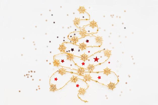 Weihnachtsbaum gemacht von der goldenen schneeflockengirlande mit silbernem sternkonfettis.