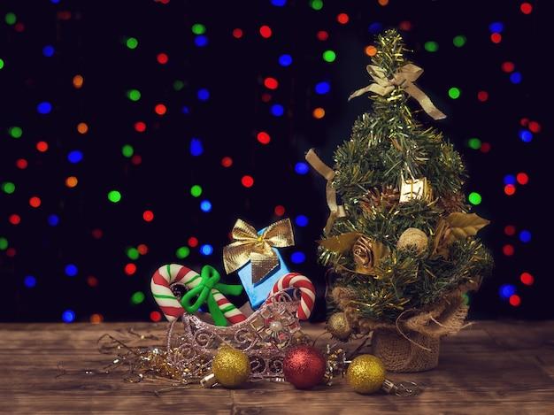 Weihnachtsbaum, geschenke und dekorationen auf dem holzboden. fröhliche weihnachten