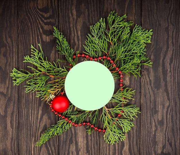 Weihnachtsbaum-hintergründe, kreativer plan gemacht von den weihnachtsbaumasten mit schnee- und papierkartenanmerkung. flach liegen. natur-neujahrskonzept.
