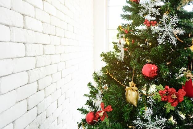 Weihnachtsbaum im grün mit rotem dekor im raum.