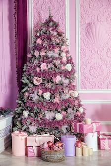 Weihnachtsbaum in rosa spielzeug verziert. weihnachtshintergrund mit geschenken im rauminnenraum