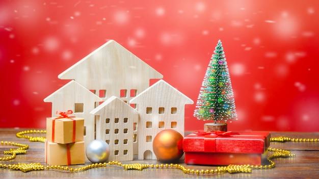 Weihnachtsbaum, miniaturholzhäuser und geschenke. neujahr oder weihnachten winterurlaub.