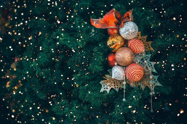 Weihnachtsbaum mit balldekoration mit licht auf baum. weihnachts- und neujahrsfeiertagshintergrund. vintage farbton. nahansicht .