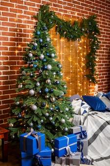 Weihnachtsbaum mit blauen und silbernen geschenken in einem weißen weihnachtsraum. schön dekoriertes haus mit silbernem und blauem baum und geschenken für weihnachten.