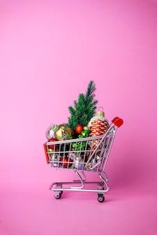 Weihnachtsbaum mit dekorationen in einem supermarktwarenkorb. weihnachtseinkauf und verkaufskonzept