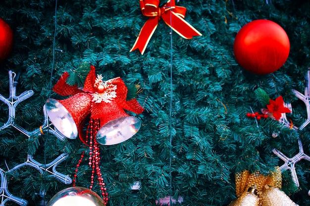 Weihnachtsbaum mit dekorationsband rote glocken und neujahrsbälle auf grünen tannenzweigen festlich am...