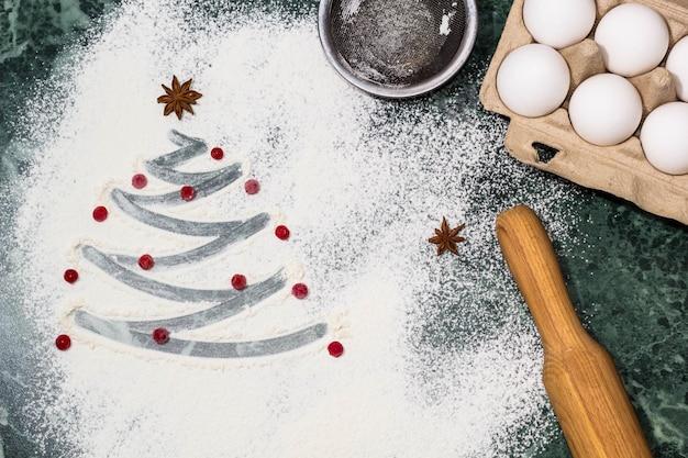 Weihnachtsbaum mit den mehl-, beeren- und anissterngewürzen als dekoration und nudelholz, eier, sieb
