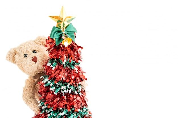 Weihnachtsbaum mit einem teddybär und er spielen suchen und verstecken fröhliche gefühle im neuen jahr.