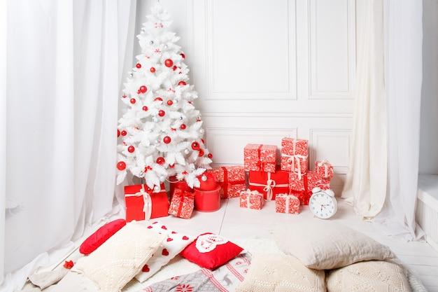 Weihnachtsbaum mit geschenken darunterliegend im weißen wohnzimmer