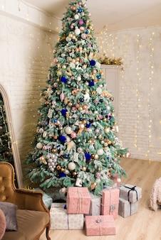 Weihnachtsbaum mit girlanden und geschenken im raum