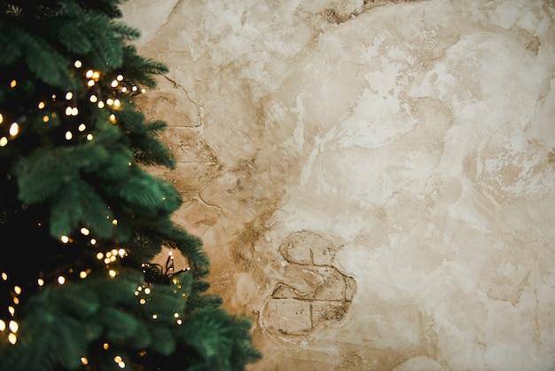 Weihnachtsbaum mit girlanden. weihnachtsbaum mit spielwaren auf einem braunen retro- wandhintergrund