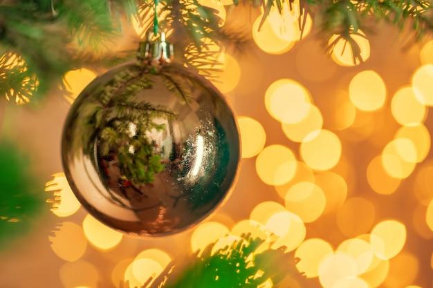 Weihnachtsbaum mit goldenem flitter auf dem funkelnden bokeh hintergrund