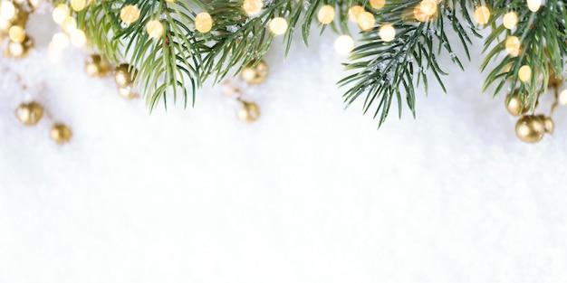 Weihnachtsbaum mit goldenen lichtern auf schnee