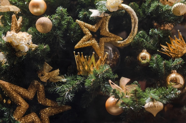 Weihnachtsbaum mit goldenen sternen und kronen geschmückt.