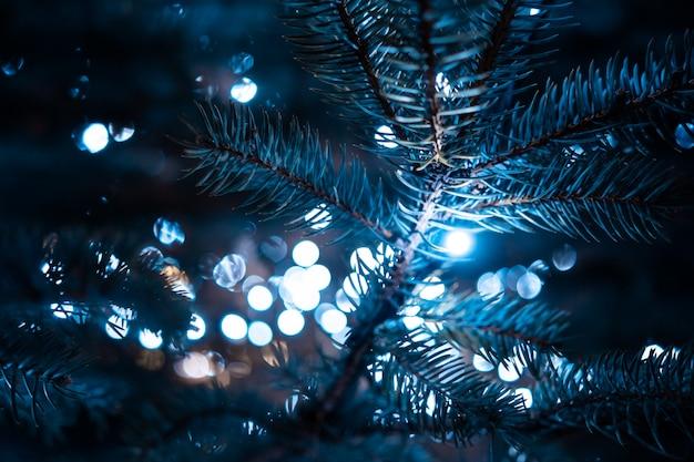 Weihnachtsbaum mit kegeln auf einer stadtstraße belichtet mit einer girlande.