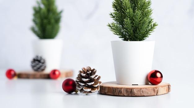 Weihnachtsbaum mit kiefernkegel und dekorweihnachtsball auf weißer tabellen- und marmorfliesenwand