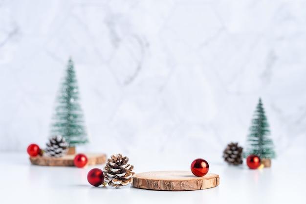 Weihnachtsbaum mit kiefernkegel und dekorweihnachtsball und leerer hölzerner klotzplatte